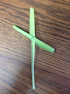 Holding cross formed from palm frond